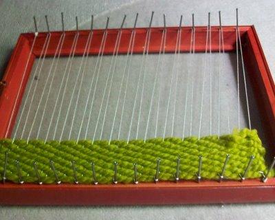 3. Работу можно сделать разноцветной, поэтому пряжа вплетается рядами разной ширины.  Не забывайте закреплять на узлы...